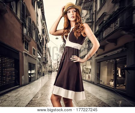 Beautiful fashion woman is wearing a brown dress and a straw hat. Posing isolated on white background