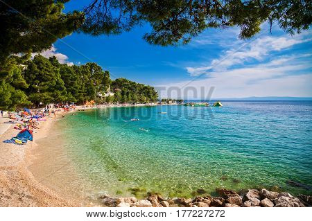 people swimming and sunbathing on a small pebble beach in Brela, Makarska Riviera, Croatia