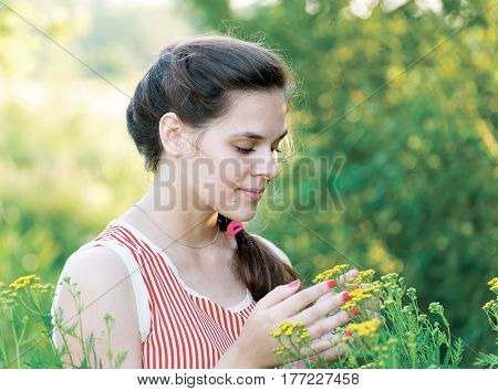 A girl looks at a tansy flowers