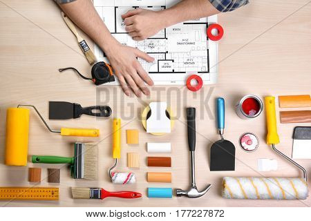 Decorator's hands on project drawing. Color swatches and tools on work table