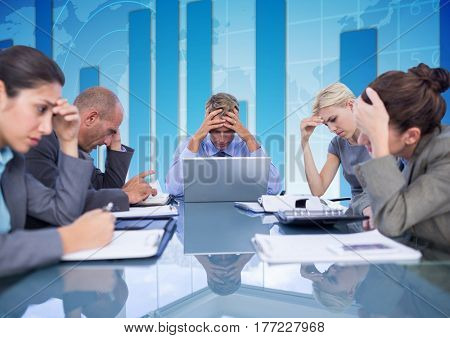 Digital composite of Business Team Seating around table looking at working paper against blue background