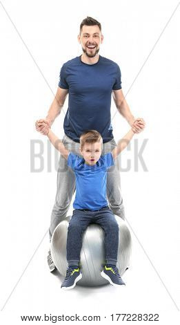 Handsome man and his son with fitball on white background