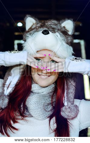 Young woman with long dyed red hair is wearing a fluffy hat with a wolf face and long pom poms, knitted scarf and hand warmers with diamond detail, and holding her hand over her green eyes.