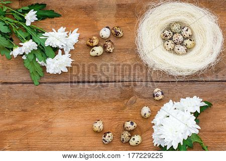 Chrysanthemum Flowers, Roses And Quail Eggs In A Nest On Old Brown Wooden Background.