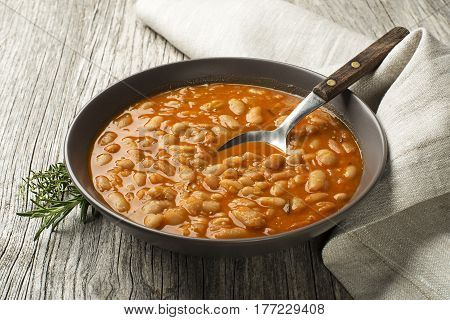 White bean stew with fresh spices on wooden table
