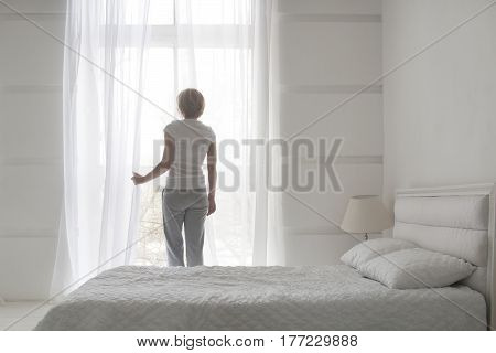 Young pretty girl opening curtains in the morning to get fresh air, back view, white concept