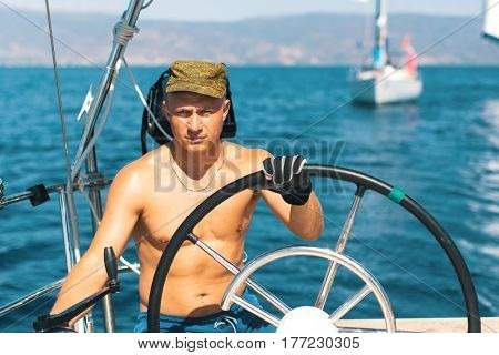 Men skipper on the yacht during the sail races in the sea. Sailing, extreme sports, luxury leisure and healthy lifestyle.