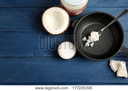 Coconut and kitchenware with fresh oil on dark blue background