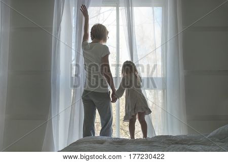 Woman and little girl, wake up and open the curtains in the spring morning, back view