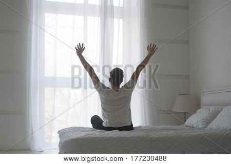 Happy young man stretching in bed after waking up, back view, total white concept