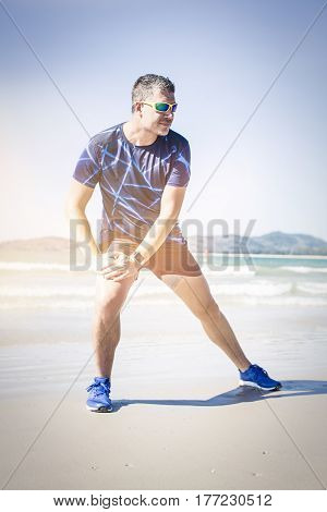 Athletic Man Stretching On The Beach