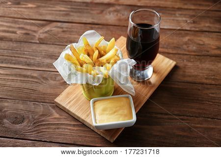 Wooden board with tasty fries, cheese sauce and glass of soda water on table