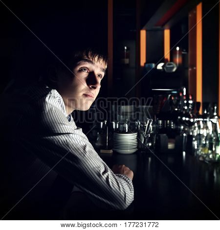Toned Photo of Young Man Sit in the Darkness at the Bar