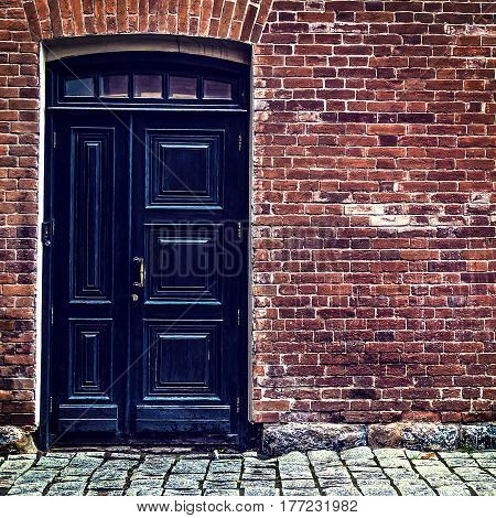 Closed Black Door and Old Brick Wall