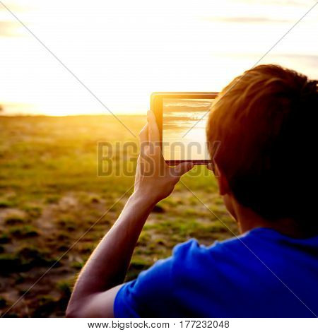 Toned Photo of Teenager take a Photo of Sunset with Tablet Computer