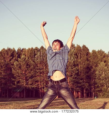 Toned Photo of Happy Young Man jumping on the Forest Background