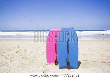 Boogie Boarding at a scenic beach. Two colorful boogie boards resting on a pristine beach.