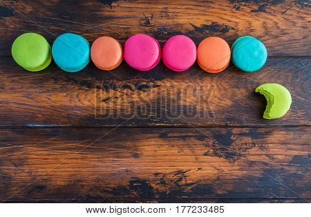 Colourful macaroons or macarons pink blue green and orange whole and bitten ones lying on the dark wooden rustic table top view.