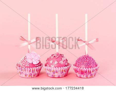 Five Romantic Pop Cake With Pink Frosting On Pink Background.