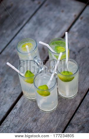 Five glasses with lemonade on a rough wooden background. Cocktails with rum, tonic and lime on a rough gray table.