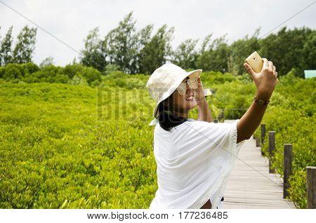 Traveler Thai Woman Use Smartphone Take Photo On Wooden Bridge For Travel And Visit Golden Mangrove