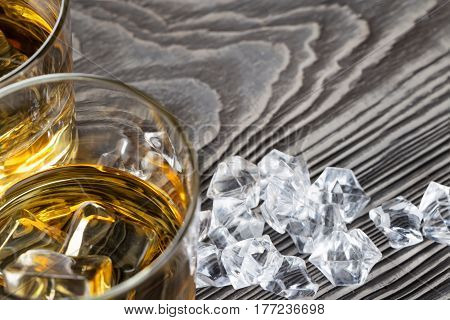 Fragment of two glasses of whiskey taken from above on a wooden background