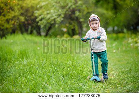 Little boy on scooter in park in Kiev Ukraine.
