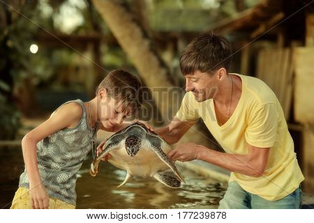 Happy dad with his son holding a large beautiful tortoise in his hands