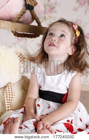 beautiful little girl looking up. Studio photography. portrait. there are a swing and a soft toy