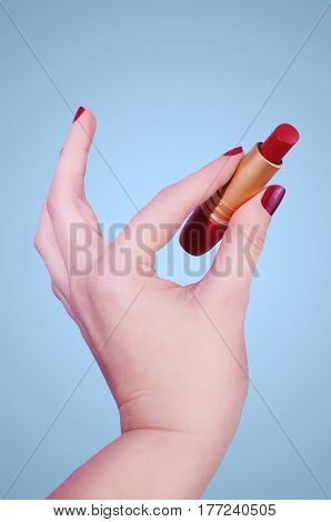 Woman´s hand holding a red lipstick on blue background.