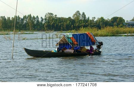 DONG THAP VIET NAM- SEPT 23 2014: Poor Vietnamese family lay on small boat floating on river at Mekong Delta family with father mother and children relax among countryside scene Dongthap Vietnam