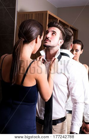 A young couple preparing to go out and getting ready and dressed in the changing room.