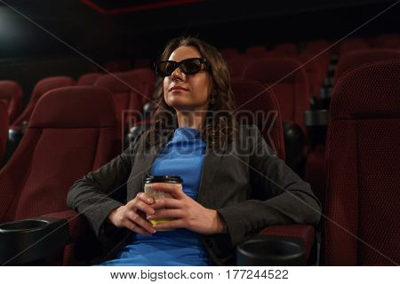Young woman watches movie 3D at the cinema and drinks coffee looking at the screen alone in an empty room overall plan