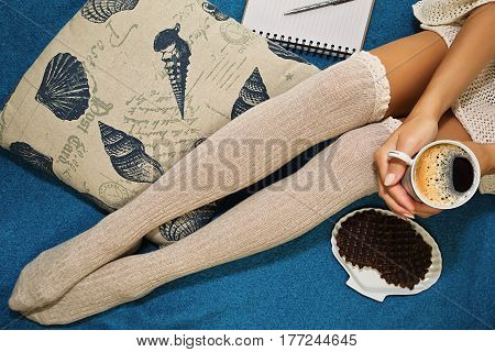 Teeanage girl in knee height socks sitting on the blue plaid with a cup of coffee and waffles planning her day with a diary and pen
