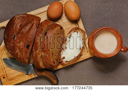 Simple but satisfying organic breakfast of traditional eastern european components - rye bread with raisins butter homemade yogurt and eggs with rural knife cutting board and mug