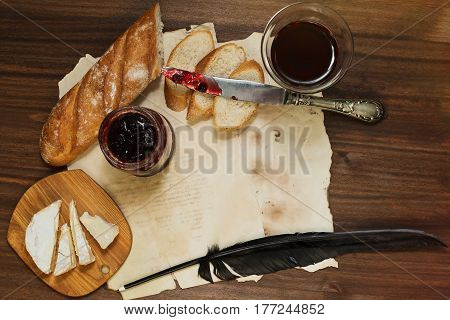 Still life in retro style with glass of red dry wine fresh baguette bread sliced camambert or brie cheese lingonberry jam antique silver knife and some vintage writing utensils
