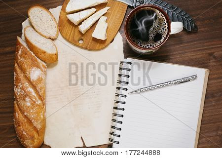 Planning the day finances or diet during the coffee break with fresh bread and refined cheese on the oldened wooden table