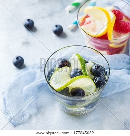 Health care, fitness, healthy nutrition diet concept. Fresh cool lemon lime berries raspberry blueberry infused water, cocktail, detox drink, lemonade for spring summer days