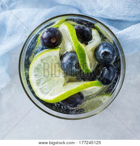 Health care, fitness, healthy nutrition diet concept. Fresh cool lemon lime berries blueberry infused water, cocktail, detox drink, lemonade for spring summer days. Top view flat lay