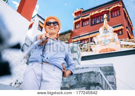 Woman take touristic self photo with tibetan monastery as background