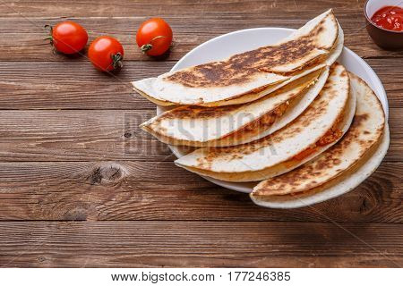 Tortilla with chicken and dressing on wooden table