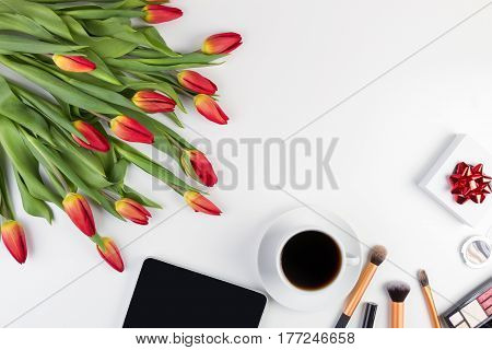 White desk with tablet computer, make up tools, cup of coffee, gift box and flowers. Top view. Flat lay
