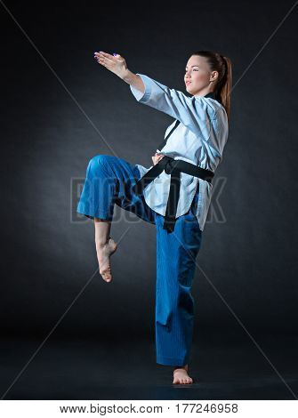 The karate girl in white kimono and black belt training karate over gray background.