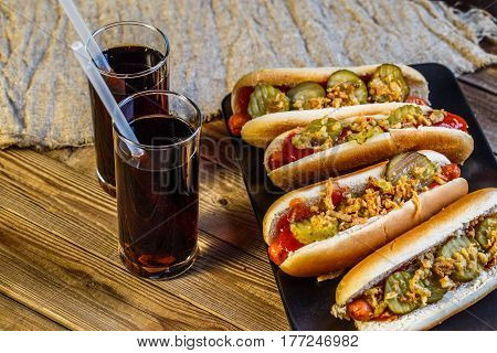 American hot dog with pickles, onions, ketchup, mustard and two soda on wood background