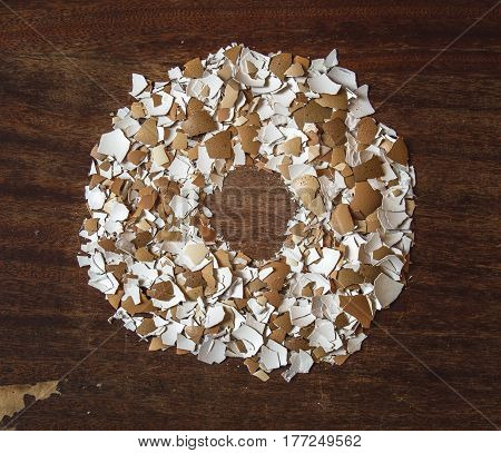 Pieces of eggshell. Many tiny details of eggshell , wood background.  Egg shell in the form of a circle