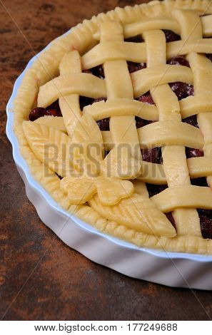 cherry pie dough with decorative ornaments in roasting pan close-up