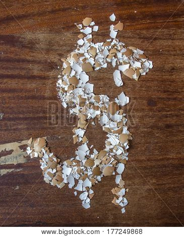 Pieces of eggshell. Many tiny details of eggshell , wood background. Egg shell in the form of a Dollar