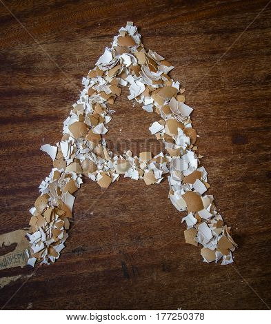 Pieces of eggshell. Many tiny details of eggshell , wood background. Egg shell in the form of letter A