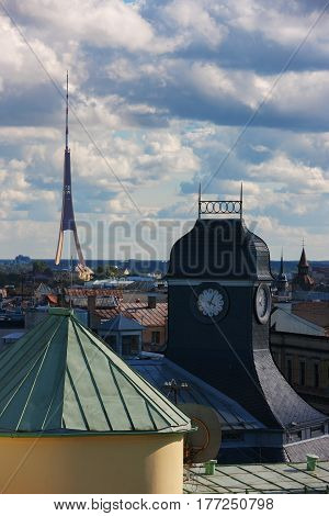 Roof and clock tower and TV tower of Riga on the background of the summer sky with clouds