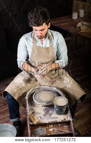 the handsome young spanish potter creating product from clay on a twisted potter's wheel. potter's wheel with the workpiece. The sculptor in the workshop.